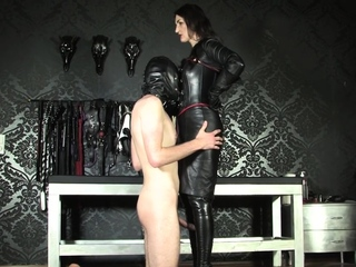 Leather mistress dominates with feet and legs